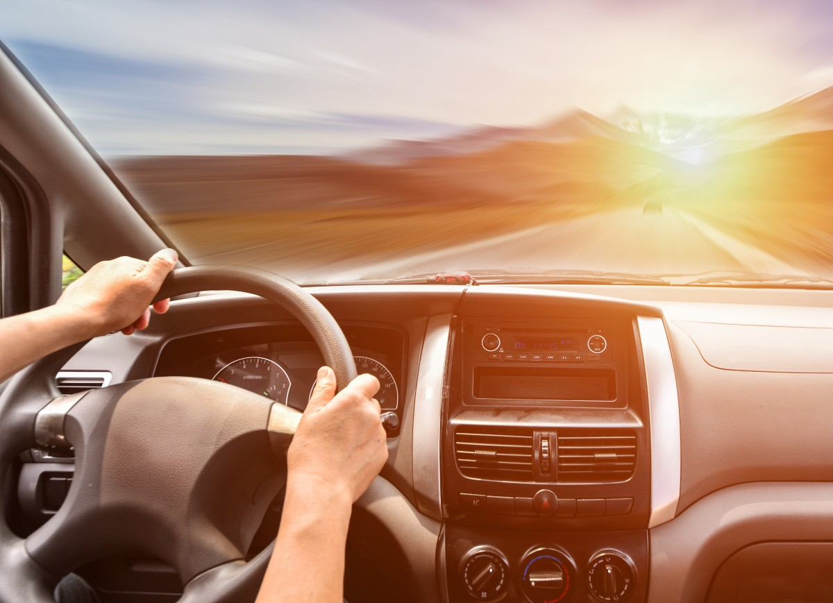 dłonie na kierownicy i widok na przednią szybę